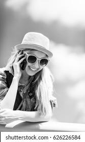 Smiling hipster girl talking mobile phone against sky