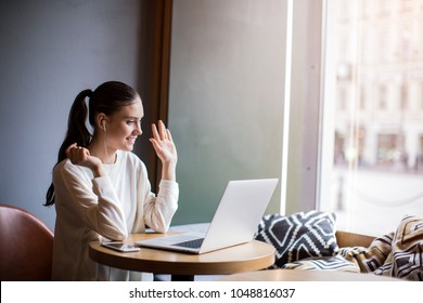 Smiling hipster girl talking and waving hand hello during online video call via laptop computer, sitting in coffee shop. Cheerful business woman having conference in internet via portable notebook