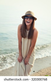 Smiling hipster girl walking on a sea beach.
