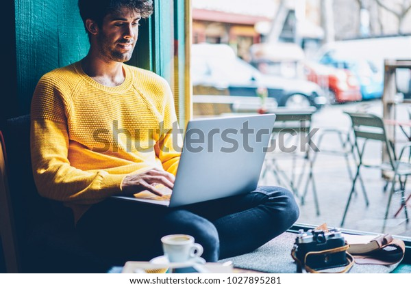 Smiling hipster guy chatting online with friends during leisure time at laptop device connected to wireless 4G internet.Cheerful male blogger publishing post on website on netbook resting in coworking
