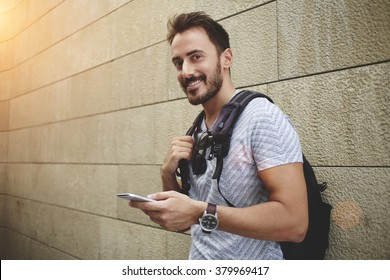 Smiling hipster guy holding mobile phone and looking at the camera while waiting for someone outdoors,cheerful man wanderer use cell telephone while standing against street wall with copy space area
