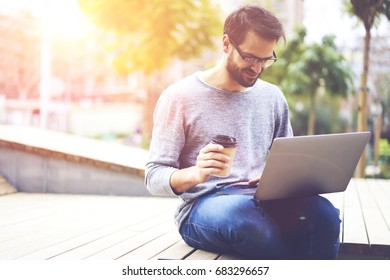 Smiling hipster guy in optical spectacles watching funny videos in social networks while enjoying tasty coffee and recreation time in urban settings.Copy space area for your advertising text message