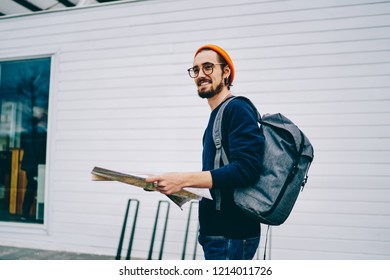 Smiling hipster guy in orange hat and with backpack strolling on urban setting having trip on vacations, cheerful caucasian male tourist walking with map get to destination in city on active rest