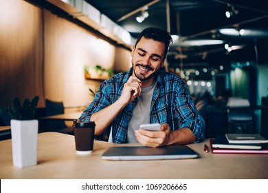 Smiling hipster guy reading new message in social networks confirming new friend on smartphone, positive young man satisfied with banking app on mobile phone checking balance while learning