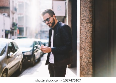 Smiling hipster guy in trendy wear chatting with friend via application on smartphone walking on city street,cheerful handsome male satisfied with internet connection uploading files outdoors
