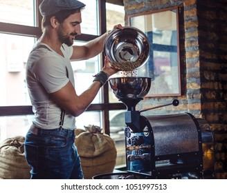 Smiling hipster man pouring raw coffee beans in a coffee roaster