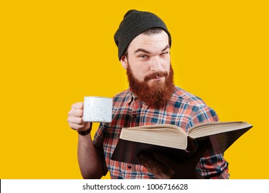 Smiling hipster man reading book with cup of coffee. Morning concept. Bearded man looking at camera. Man with cup of tea or coffee and book over orange background.