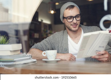 Smiling hipster man reading book at cafe