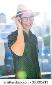 Smiling hipster using his phone in his office