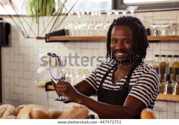 Smiling hipster worker wiping glasses at cafe