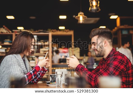 Smiling hipsters in cafe using their smartphones.