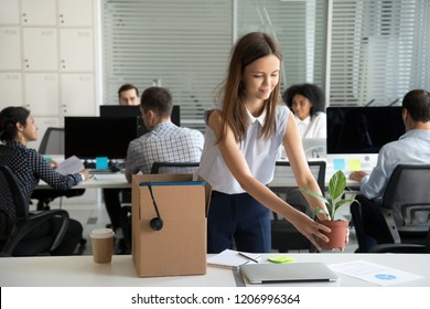 Smiling hired female company employee unpacking box with personal belongings at workplace on first working day in shared office, happy intern or newcomer got new job excited to start work concept