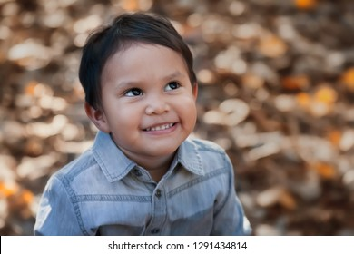 A smiling hispanic boy looking up, gazing into the sky with an expression of hope or day dreaming positive thoughts.