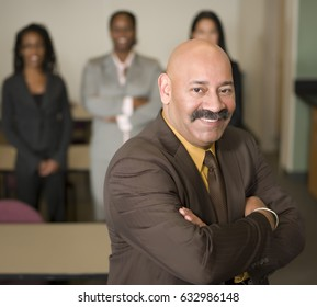 Smiling Hispanic businessman with arms crossed