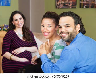 Smiling Hispanic couple sitting with beautiful surrogate mother