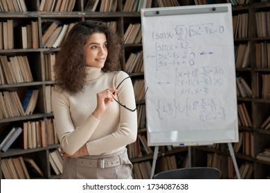 Smiling hispanic dreamy young adult woman university math teacher, professional school tutor, female latin student looking away dreaming thinking of new opportunities concept standing in classroom.