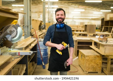 Smiling hispanic man doing carpentry work in a woodshop. Happy carpenter working with a power drill and a hammer