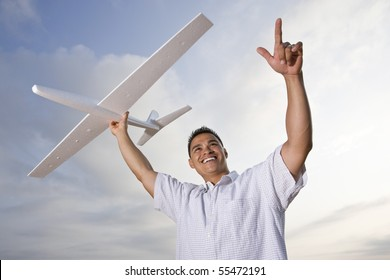 Smiling Hispanic man holding model airplane glider over head