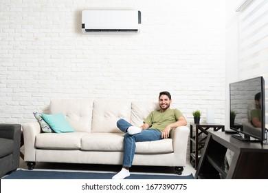 Smiling Hispanic man resting on sofa below air conditioner at home
