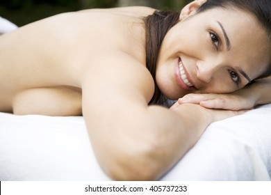 Smiling Hispanic woman on a massage table in a tropical setting