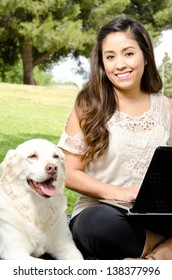 a smiling Hispanic woman sitting in the park with her dog and a computer.