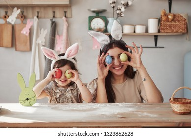 Smiling and holding eggs. Mother and daughter in bunny ears at easter time have some fun in the kitchen at daytime.