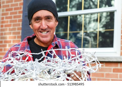 smiling home owner handing over a tangled bundle of outdoor Christmas lights