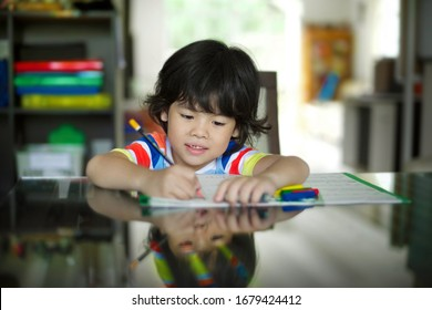 Smiling homeschooling kindergaten boy doing Singapore math at home.Little preschooler holding a pencil to solve mathematics word problems.Homeschooler calculates maths with tools.Asian kid studying.