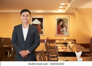 Smiling hospitable Vietnamese restaurant manager