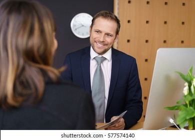Smiling hotel manager or receptionist attending to a female client in a classy hotel standing with her bill or a brochure in his hand