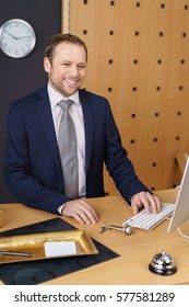 Smiling hotel manager or receptionist working on a desktop computer entering data with a door key ad service bell alongside on the wooden counter