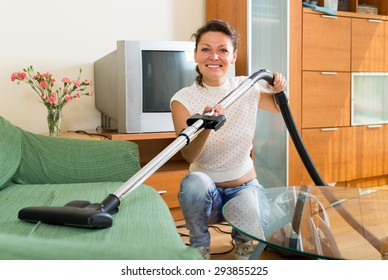 Smiling housewife cleaning sofa with vacuum cleaner at living room