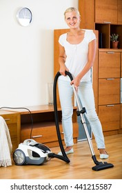 Smiling housewife in jeans vacuuming floor and furniture