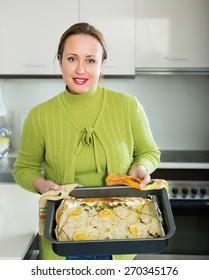 Smiling  housewife preparing slices of white fish for baking