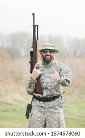 The smiling hunter or military person with gun or rifle is showing thumb ups outdoors.