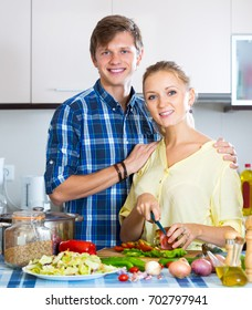 Smiling husband helping wife to prepare healthy dinner