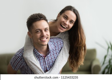 Smiling husband piggybacks cheerful wife at home, millennial couple in love embracing looking at camera, young real estate owners having fun in new house, happy man and woman dating headshot portrait