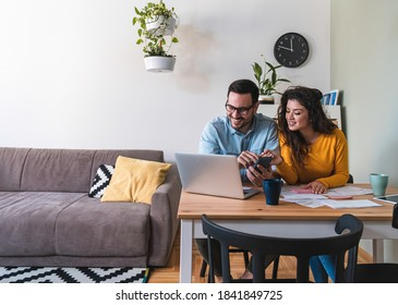 Smiling husband and wife paying bills online
