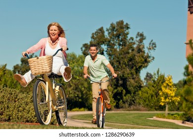 Smiling husband and wife riding bicycles.