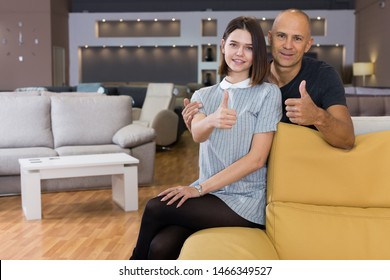 Smiling husband and wife showing thumbs up sitting on sofa in furniture salon