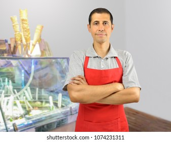 Smiling ice cream store employee standing behind the counter in the store with crossed arms
