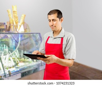 Smiling ice cream store employee standing behind the counter in the store and uses a digital tablet