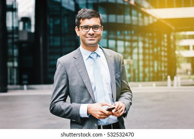 Smiling indian business man with smartphone