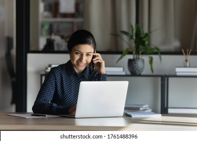 Smiling Indian businesswoman feels satisfied confident provide help consulting client distantly by mobile phone call seated at desk in modern office. Busy fruitful workday, successful employee concept