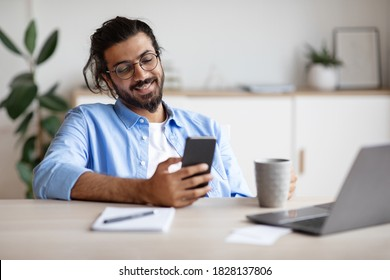 Smiling Indian Employee Using Smartphone And Having Coffee In Office, Enjoying Break At Work, Texting With Friends Or Browsing Social Networks, Sitting At Desk With Laptop, Selective Focus, Free Space