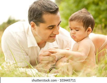 Smiling Indian Father with Baby Son Outdoors on Grass