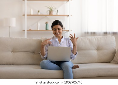 Smiling indian female teacher sit on sofa at living room explain new information to pupil before laptop webcam on distance. Pleasant young lady share news answer question talk by video call using pc