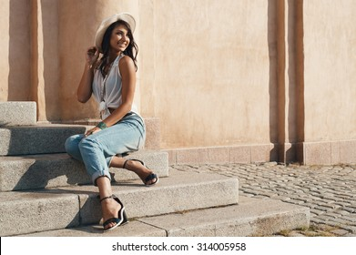 smiling indian lady in jeans, white shirt and white hat against ancient building. She is in harsh morning light. She is positive and playful.