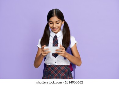Smiling indian latin preteen kid girl wears school uniform holds backpack and phone watching mobile streaming ad, remote learning online class, video calling on cellphone isolated on lilac background.
