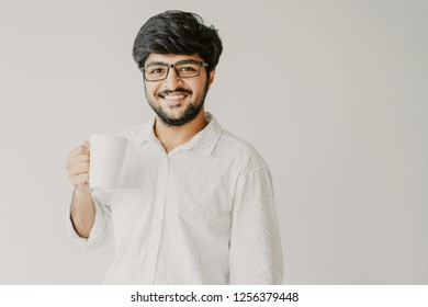 Smiling Indian man holding mug and looking at camera. Young guy drinking tea or coffee. Break concept. Isolated front view on grey background.